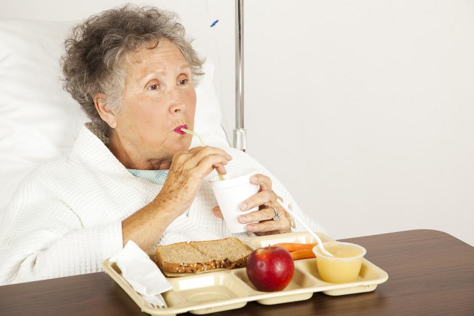 Пожилая пациентка пьёт с помощью трубочки