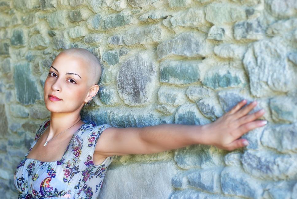 Девушка без волос около стены