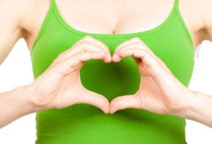 Девушка в зелёном топике показывает сердце