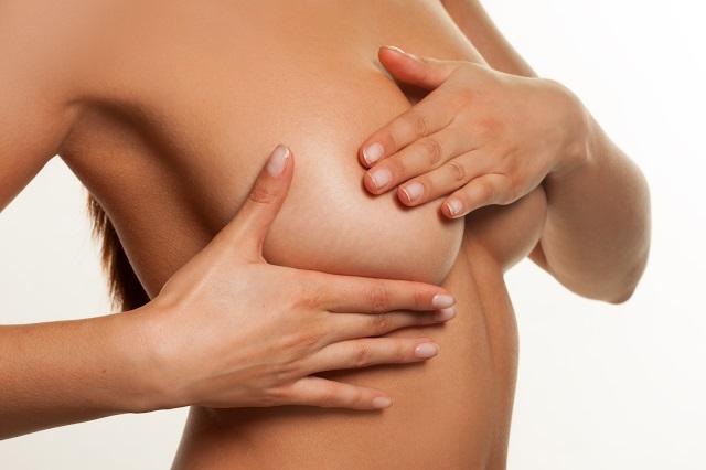 Женщина ощупывает молочную железу