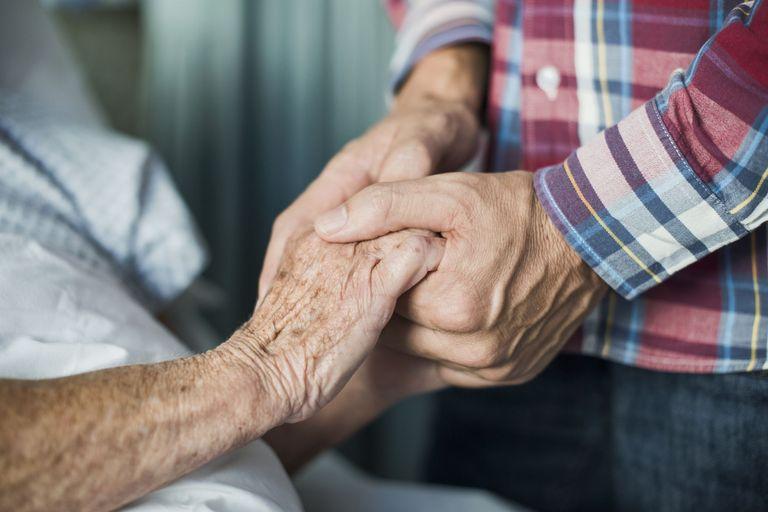Мужчина в рубашке держит за руку пациента
