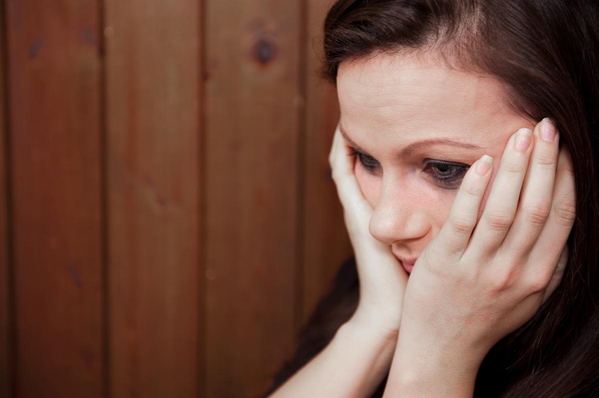 Печальная женщина держит голову руками
