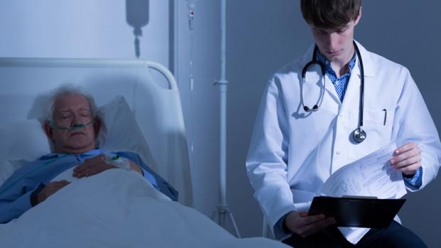 Молодой врач у постели пожилого больного
