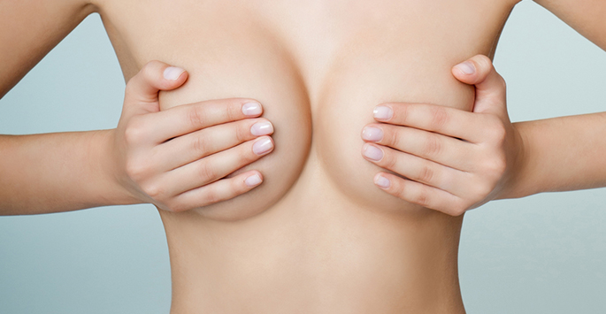 Женщина прикрывает руками грудь